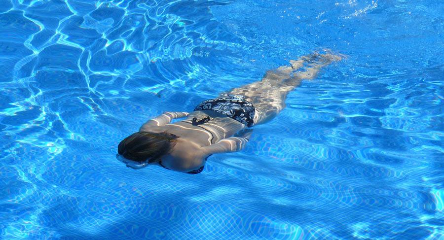 Frau taucht im eigenen Pool